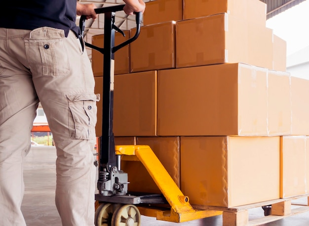 Worker man unloading shipment package boxes on pallet with hand pallet truck