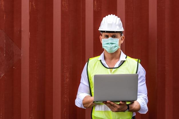 汚染とウイルスを防ぐためにラップトップwaringサージカルマスクを使用して労働者の男