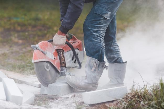 Рабочий-каменщик режет тротуарную плитку циркулярной пилой во время ремонта тротуара на городской улице