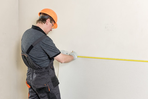 Worker measured to cut off a piece of drywall later