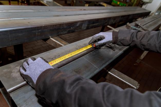 Рабочий измеряет отметки на металлической поверхности для сверления отверстий. маркировочные инструменты.
