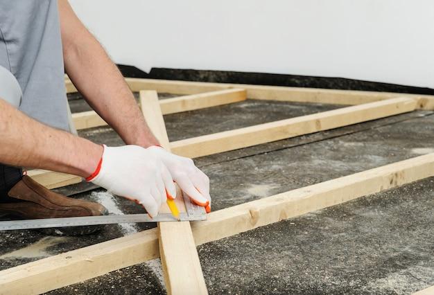 労働者は木製の梁を測定します。