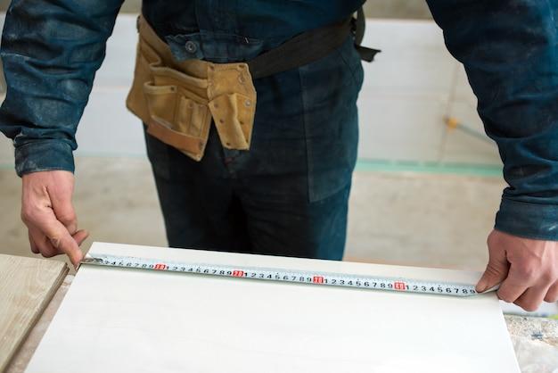 Рабочий измеряет длину настенной плитки