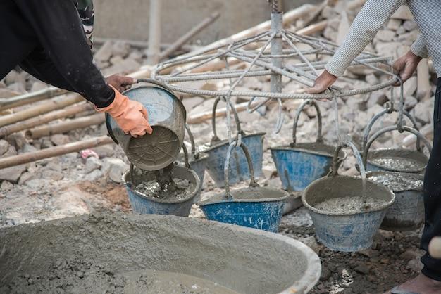 Рабочий смешивания раствора в ковше у строителя