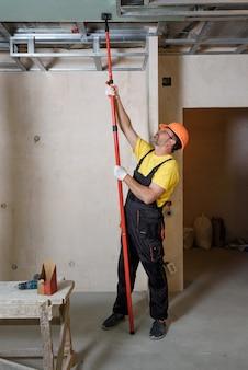 Рабочий монтажник гипсокартона прижимает гипсокартон к потолку.