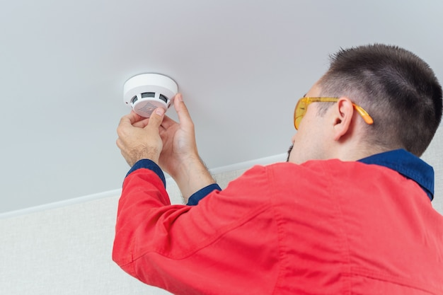 Worker mounting fire alarm on the ceiling