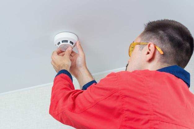 労働者が天井に火災警報器を取り付け