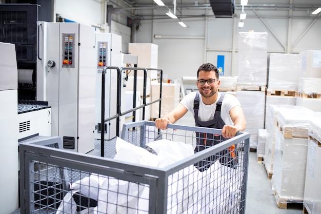 印刷所で古紙でいっぱいのカートを移動する労働者。