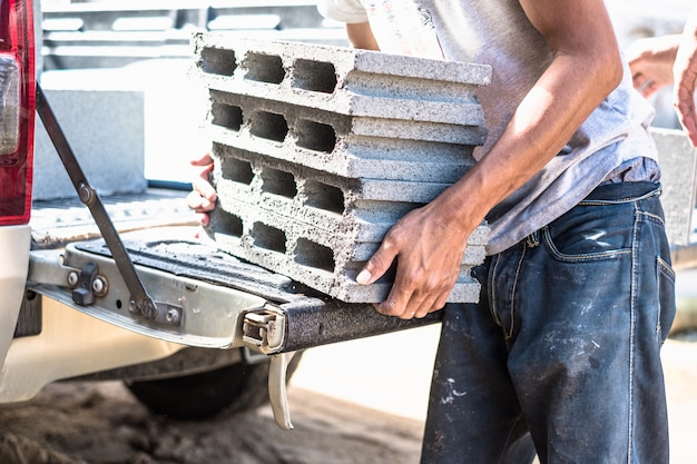 トランク車のピックアップから重い建材を移動する労働者。