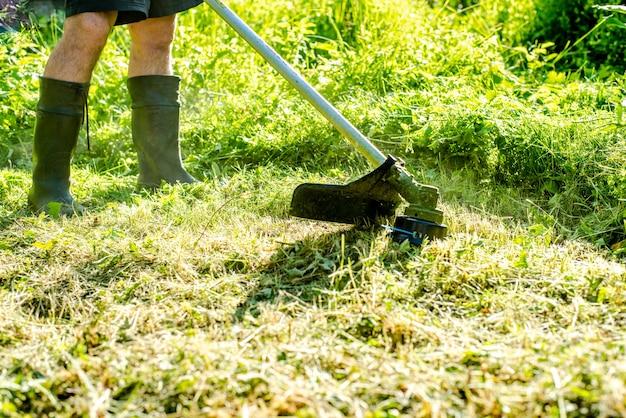 도시 공원이나 뒤뜰에서 전기 또는 가솔린 잔디 트리머로 키 큰 잔디를 깎는 작업자 원예 관리 도구 및 장비 손 깎는 기계로 잔디를 다듬는 과정
