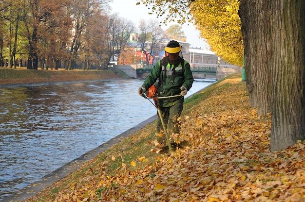 A worker mows grass with a petrol scythe near mikhailovsky park in st. petersburg