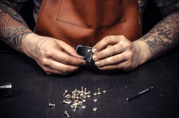 가죽을 자르는 가죽 작업자가 작업장에서 새로운 생산을 위해 개요를 설명합니다.