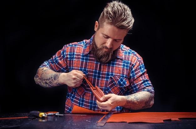 Кожевник производит изделия из кожи в кожевенном магазине.