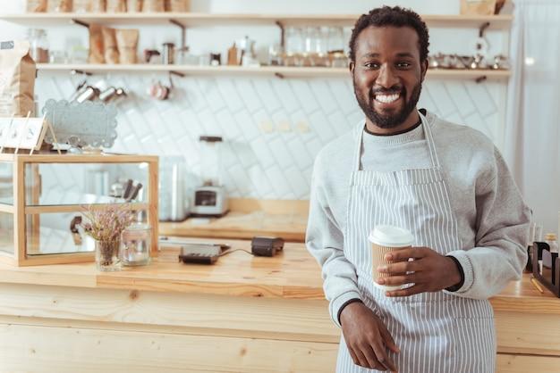 月の労働者。カフェのカウンターの前に立って、広く笑顔でコーヒーを飲みながらポーズをとるエプロンでハンサムな楽しい若いバリスタ