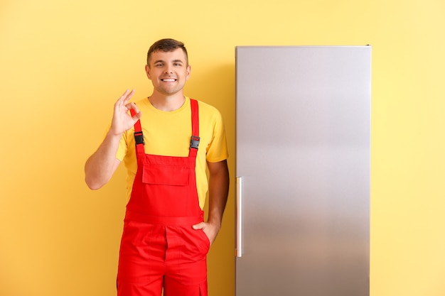 Работник службы ремонта показывает ок возле холодильника на цветном фоне