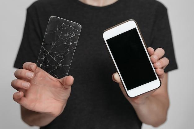 Работник сервисного центра, держа в руках смартфон и сломанную защиту экрана