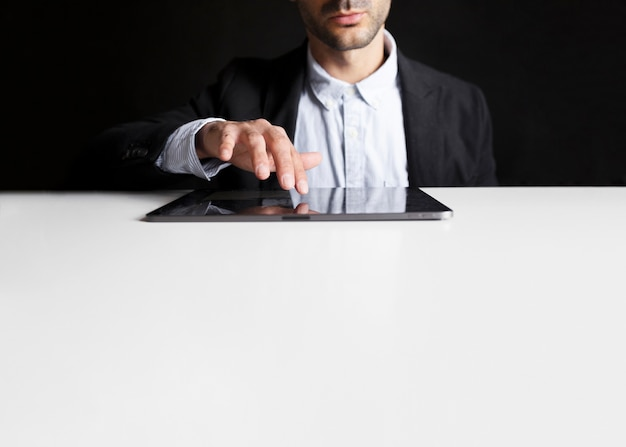 Lavoratore in ufficio utilizzando una tavoletta in bianco e nero