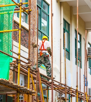 Рабочий на строительных лесах ремонтирует здание.
