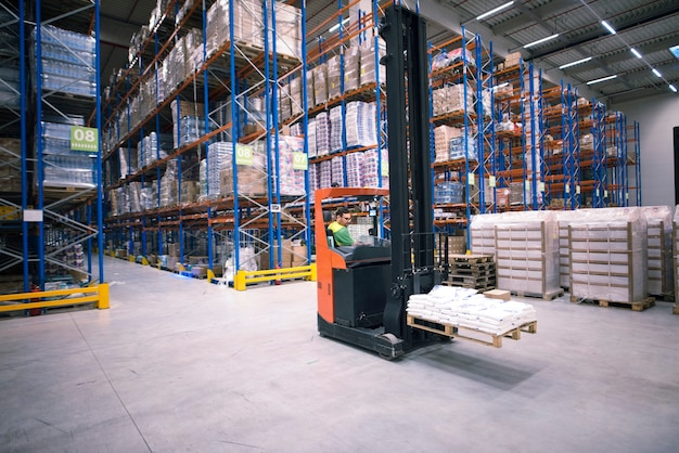 Worker operating forklift machine and relocating goods in large warehouse center