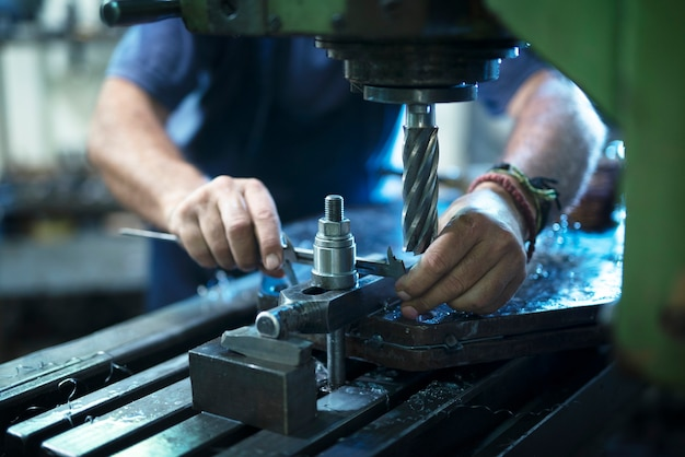 금속 워크숍에서 산업 기계를 작동하는 작업자