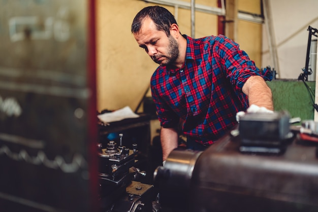Worker operating lathe machine in the industrial factory