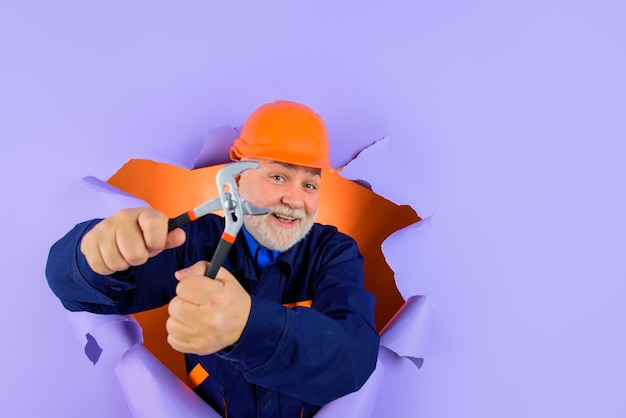 종이 전문 배관공을 통해 보는 펜치가 있는 헬멧을 쓴 작업자 또는 빌더는 펜치를 자동으로 보유합니다.