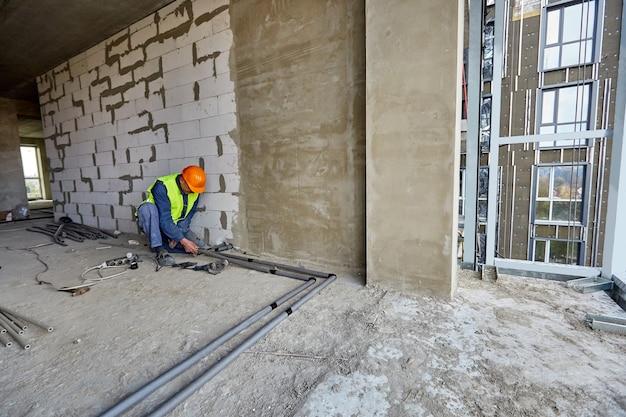防護服と安全ヘルメットの労働者またはビルダーは、建設中の建物のフラットに最新のツールを使用してプラスチックパイプを設置しています