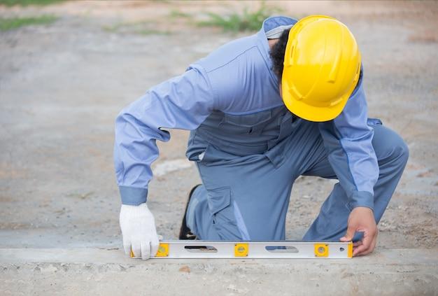 시멘트 측정을 위해 물 통치자 또는 게이지를 사용하여 작업 현장에서 작업자 또는 목수