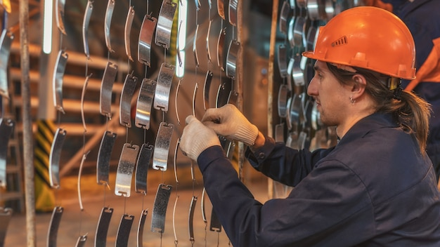 A worker in an orange helmet prepares the parts for painting