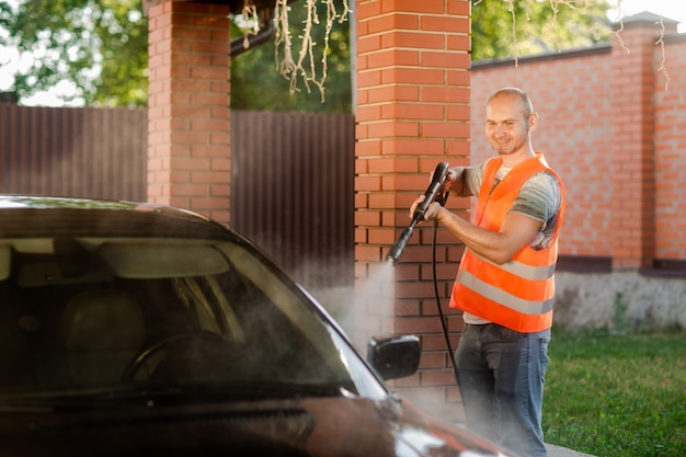 A worker in an orange vest washes the car.
