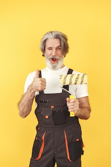 Operaio in tuta. uomo con strumenti. senior con rullo di vernice.