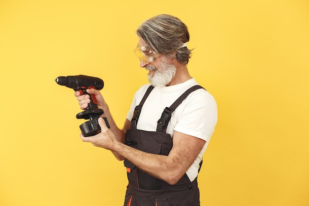 Worker in overalls. man with tools. senior with screwdriwer.