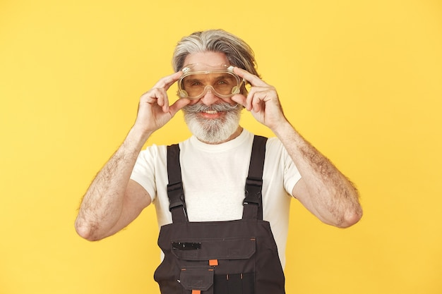 Worker in overalls. man with tools. senior in yellow glasses.