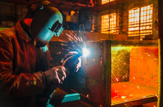 The worker in overalls and a protective mask welds metal with a welding machine