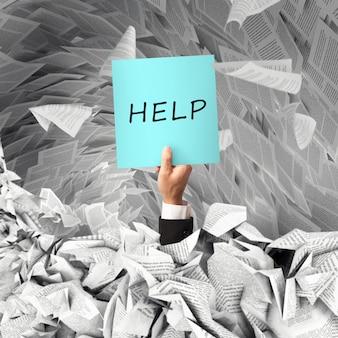 서류 작업에 압도된 작업자가 침몰할 때 손에 사인을 들고 도움을 요청합니다.