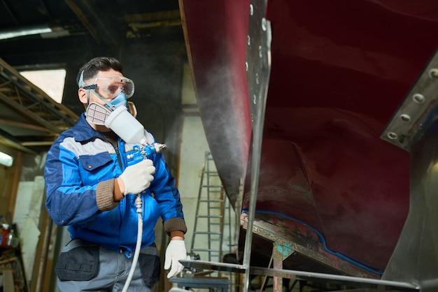 Рабочий красит лодки в яхтенной мастерской
