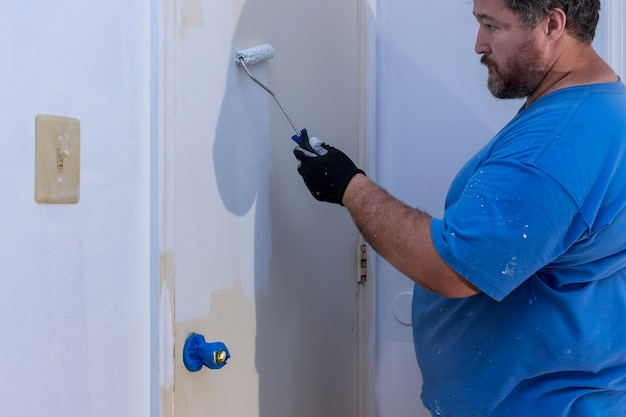 Worker painting using paint roller on layer white color a door frame trim at home renovation