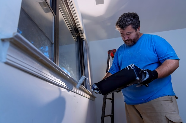 Worker painting using paint roller on layer white color a window frame trim at home renovation