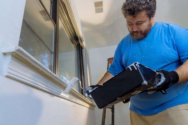 家の改修でレイヤーホワイトカラーウィンドウフレームトリムにペイントローラーを使用して作業者の塗装