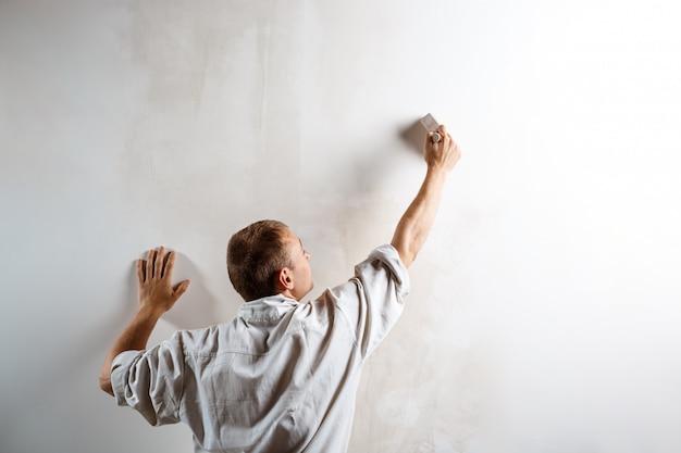 Рабочий красит стену кистью в белый цвет.