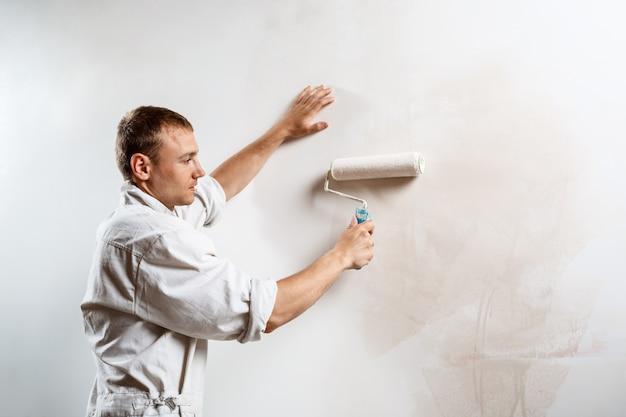 Рабочий красит стену валиком в белый цвет.