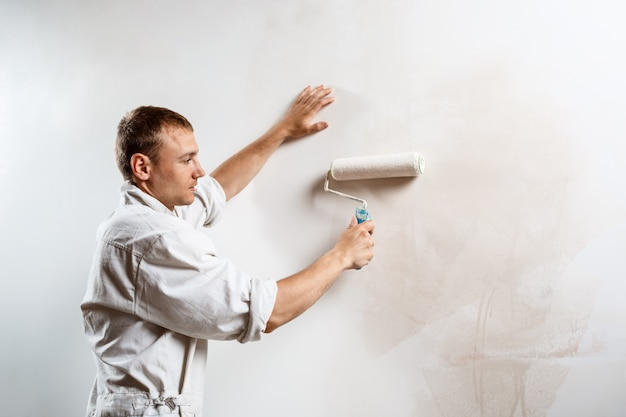 Worker painting wall with roller in white color.