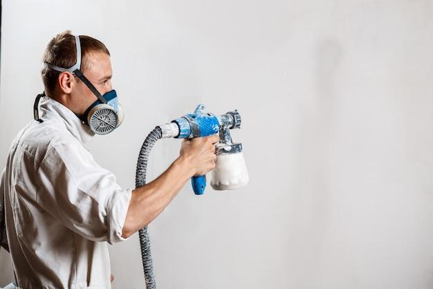 Рабочий красит стену распылителем в белый цвет.