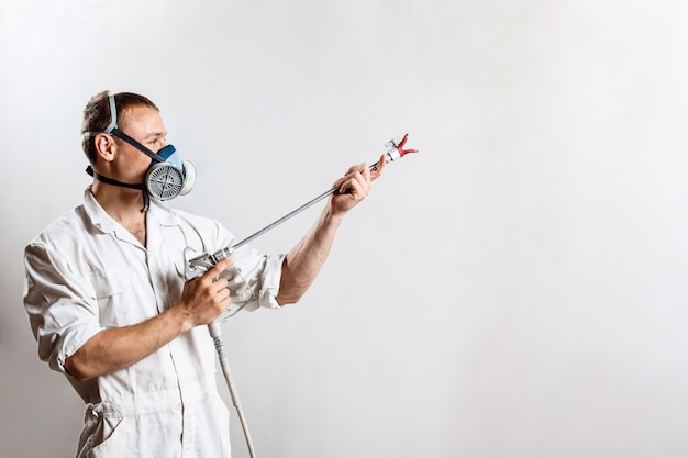Worker painting wall with spray gun in white color.
