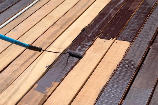 木の床にペイントローラーで塗装する労働者