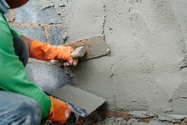 Worker plastering cement on wall for building house