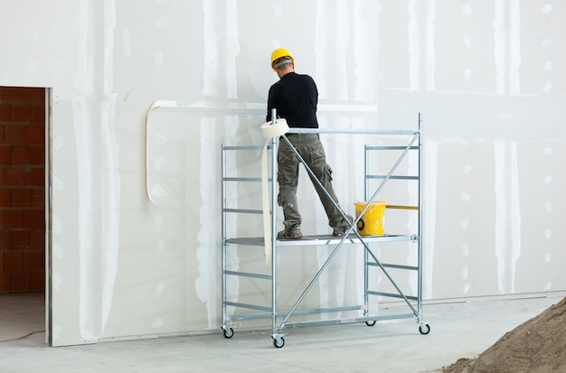 Worker plastering gypsum board wall.