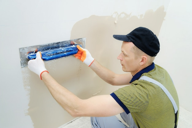Worker plastering a wall in a apartment from the bottom up