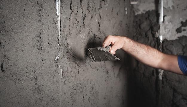 Рабочий оштукатуривает стену. строительные работы