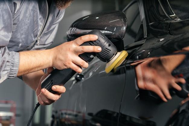 Рабочий полирует машину специальной шлифовальной машиной и воском от царапин на автосервисе. профессиональная концепция детализации и обслуживания автомобилей